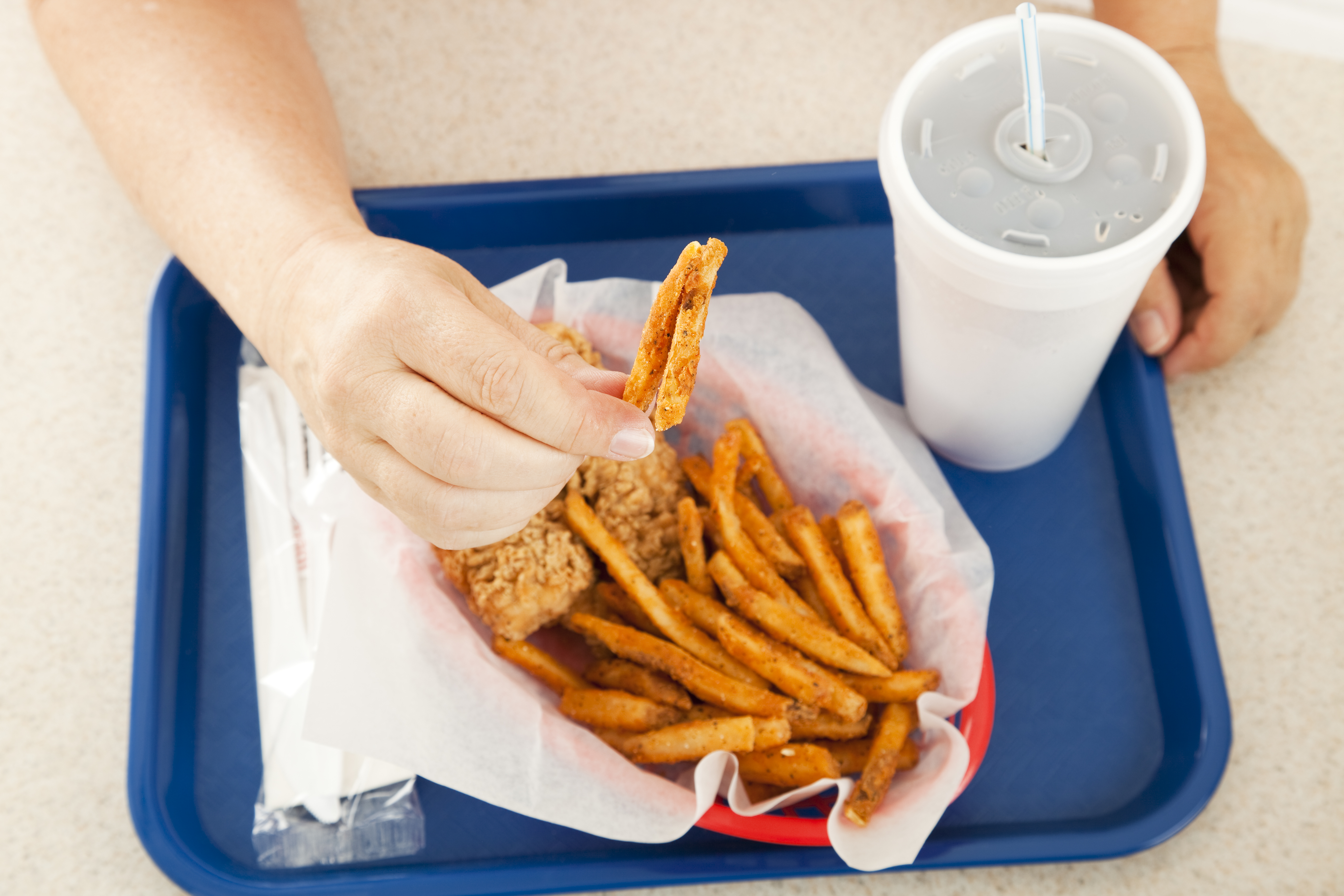 A plate of greasy fast food, with the customer holding up a greasy french fried potato to the camera.  Focus on the hand and the fry.