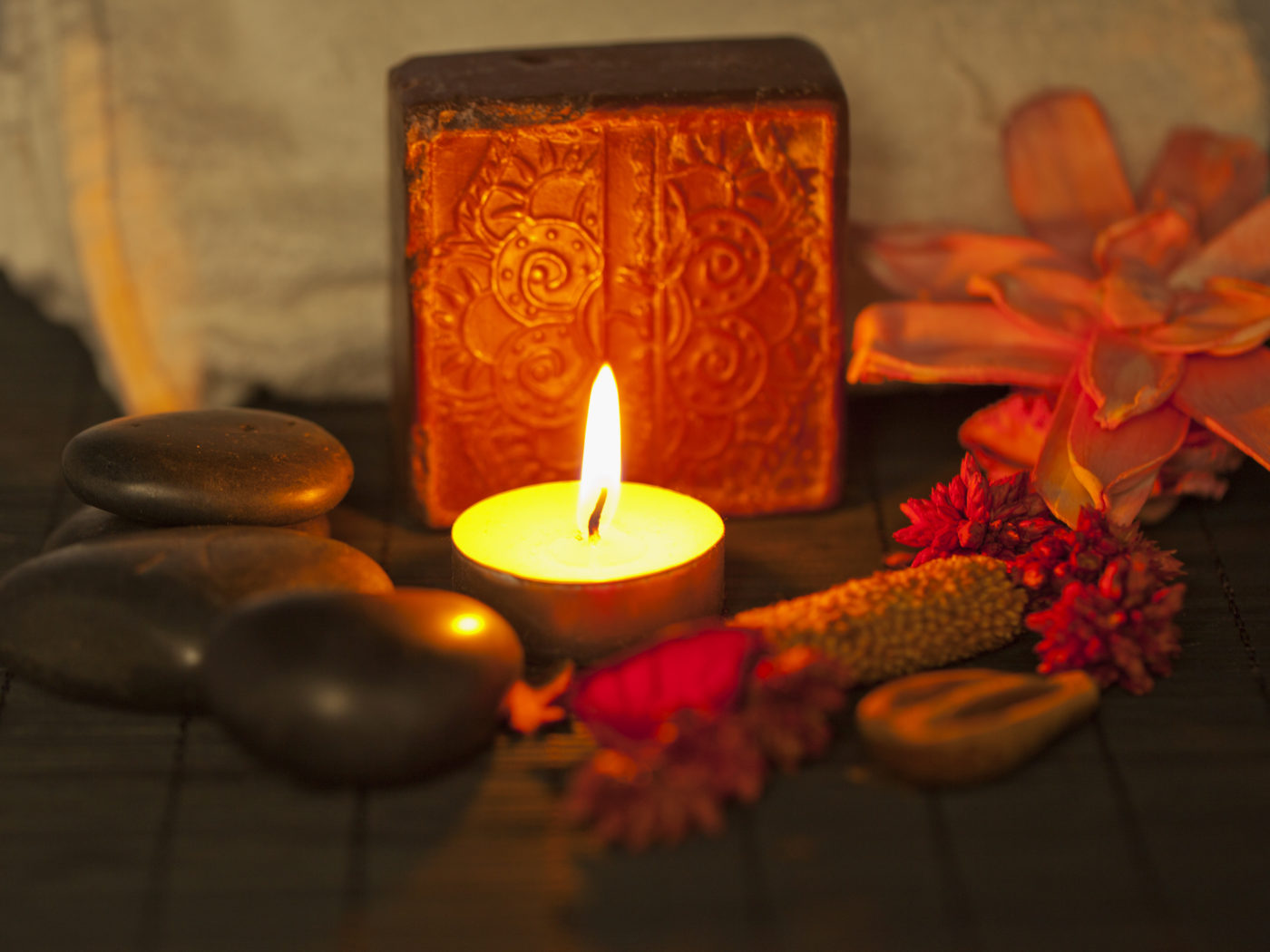 Brown soap, candle, stones and towel over wooden background