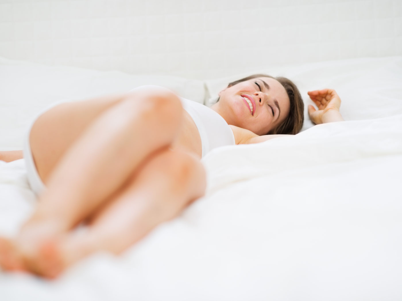 Happy young woman laying on bed
