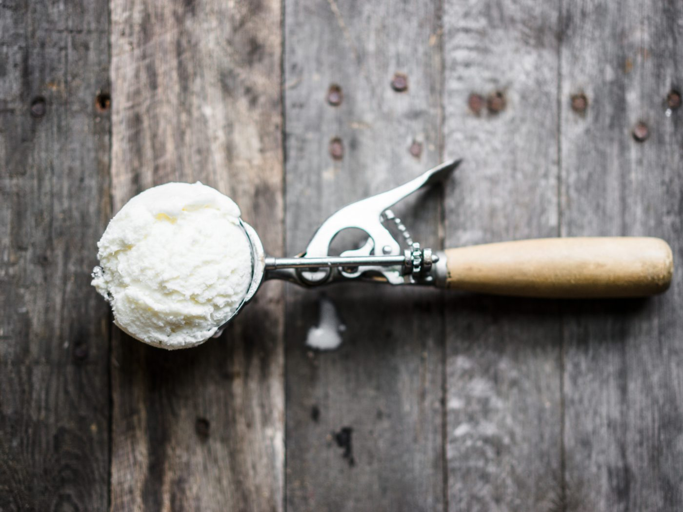 Scoop of vanilla ice-cream on rustic wooden background