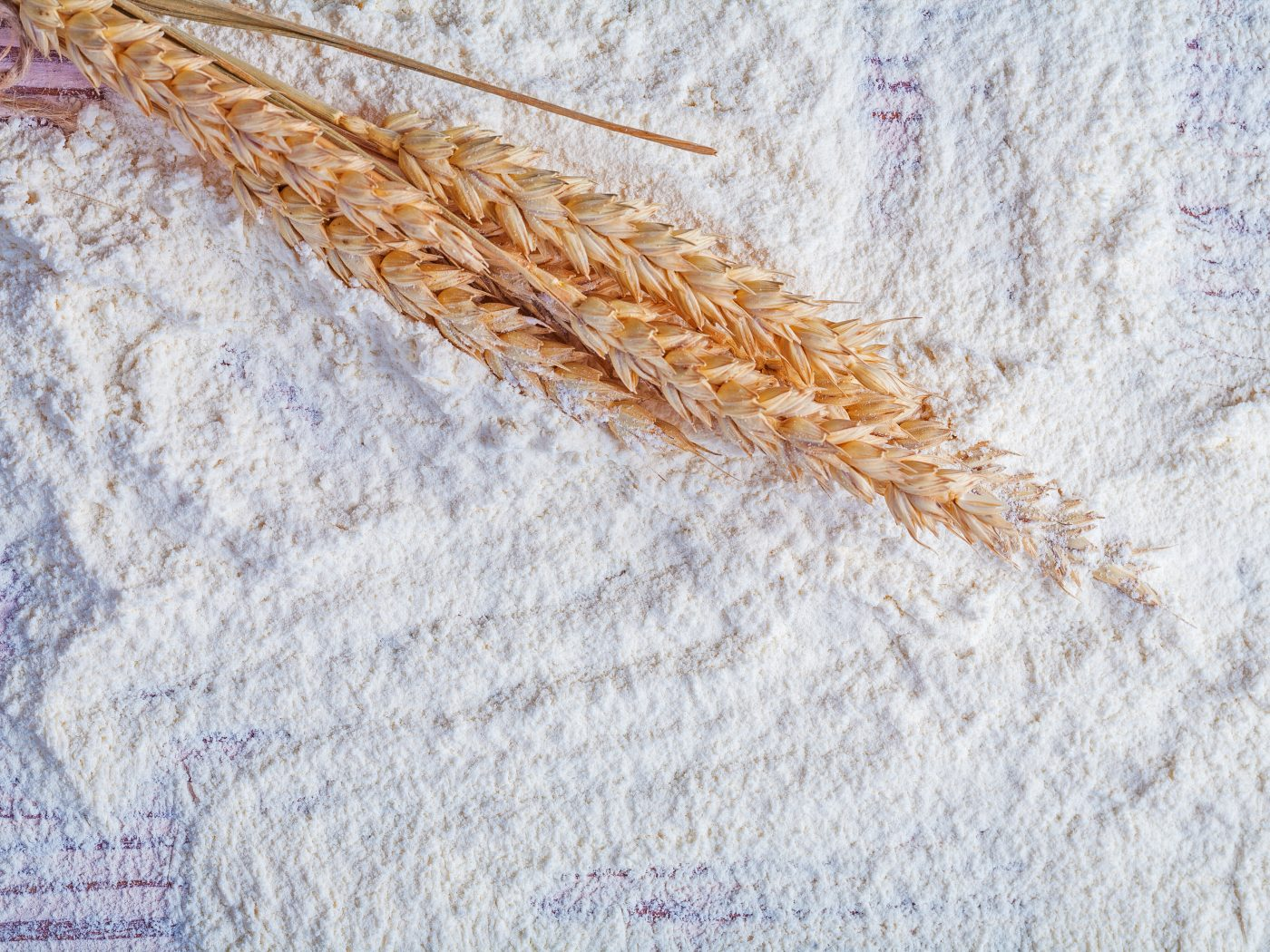 small bunch of wheat ears on flour food and drink concept