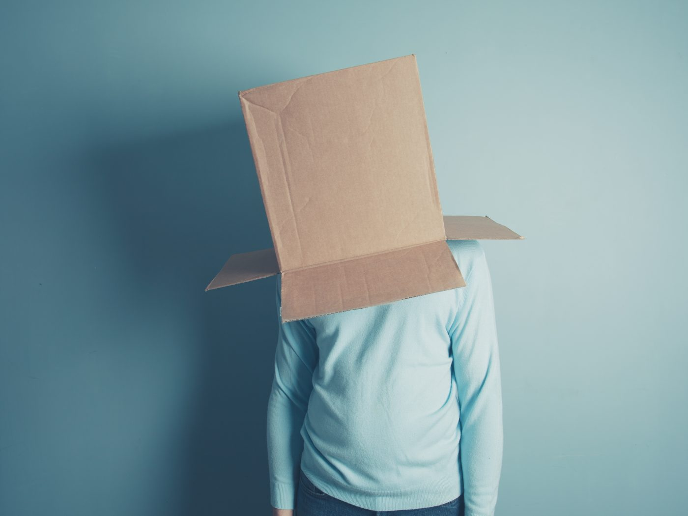 A man is standing with a cardboard box over his head